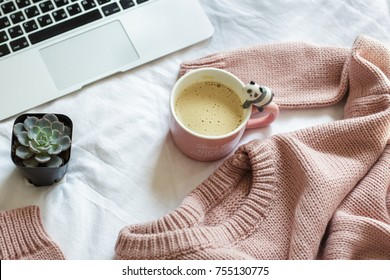 pink knitted sweater, flower, a cup of coffee and a laptop lie on the bed in the bedroom