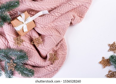 Pink knitted sweater with gift box, christmas decoration and fir branches on a white background, top view. Christmas still life