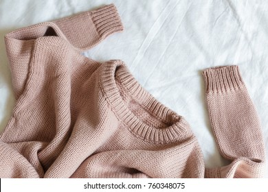 07b8fca6ea44 pink knitted sweater lies on a white blanket