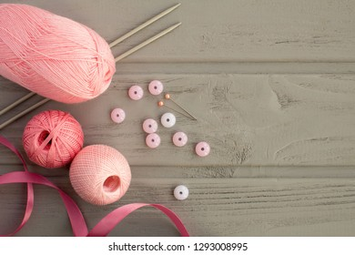 Pink knitting and knitting needles on the grey wooden background.Top view.Copy space.