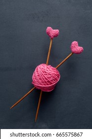 Pink knitting wool and knitting needles. Knitting needles with crochet pink hearts.