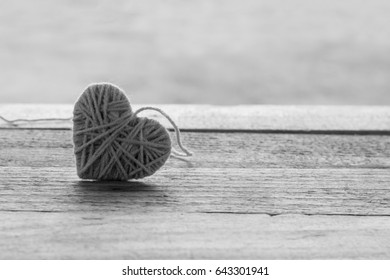 pink knitting wool in shape of heart on vintage wooden with bokeh soft light background, black and white style