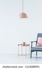 Pink lamp above copper table next to a blue armchair in pastel living room interior with copy space. Paste your armchair here