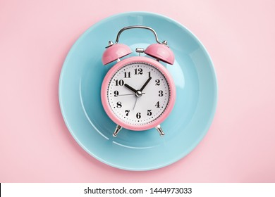 Pink larm clock on empty blue plate. Concept of intermittent fasting, lunchtime, diet and weight loss