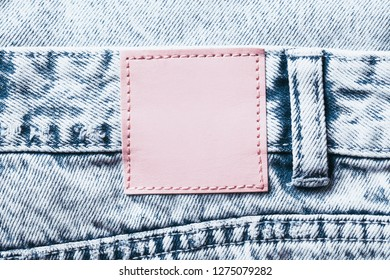 Pink leather empty copy space label on blue jeans denim background.