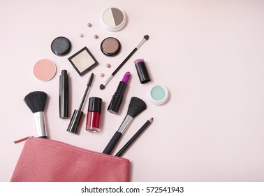 A pink leather make up pouch with cosmetic beauty products spilling out on to a pastel background, with blank space at side