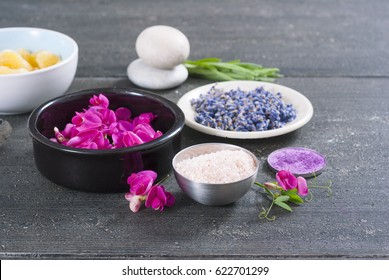 pink linaria flowers and bath salt, dried lavender buds on black wood table