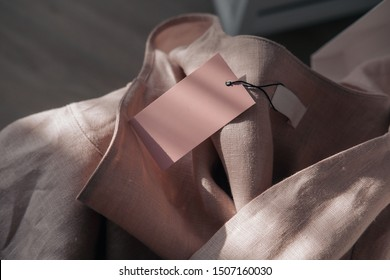 Pink linen dress with tag.  Branding mock up. Fashion blogging concept. Direct sunlight, lights and shadows photography.