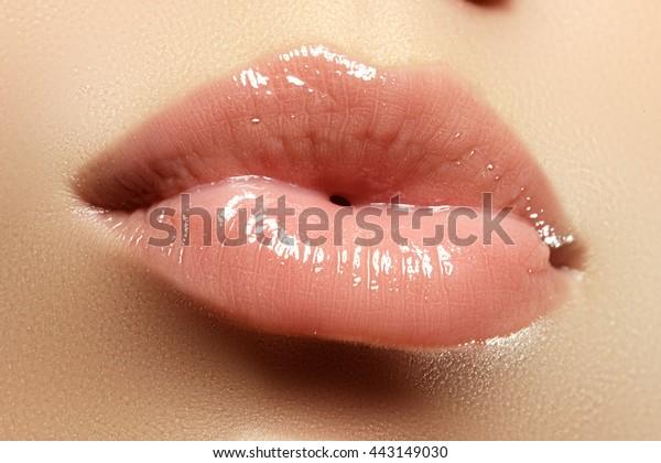 ピンクのリップグロスと口紅。美しいセクシーな自然の唇の接写、キス。光沢のある口紅のすてきなフルリップ。ファッションメイク。セクシーな唇。美しい唇が細かく