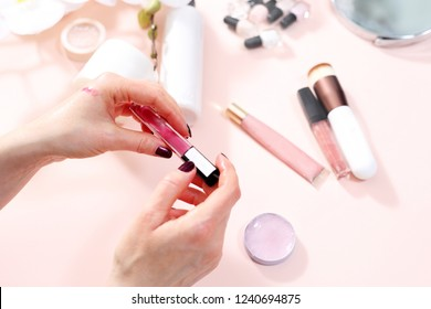 Pink lip glosses, colorful cosmetics. The woman chooses a shade of lipstick.