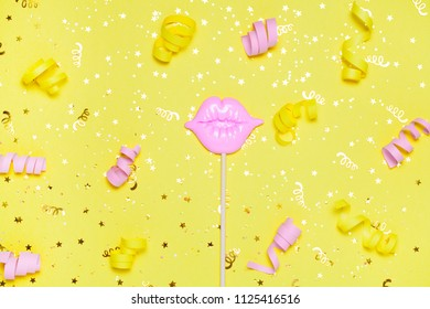 pink lips for fun on yellow festive background with golden confetti. Bright celebration concept. Top view, flat lay. Copy space for text.