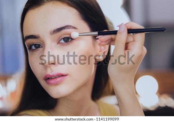 ピンクの唇。化粧をしながらアイシャドウを使ってピンクの唇を持つ緑の目をした美しい女性