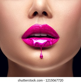 Pink Lipstick dripping. Paint drips from the lips, lipgloss dripping from sexy lips, Purple liquid drops on beautiful model girl's mouth, creative abstract make-up. Beauty woman face makeup close up