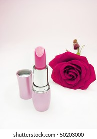 pink lipstick in gold box with damask rose on background