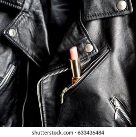 Pink lipstick in a pocket of a studded jacket