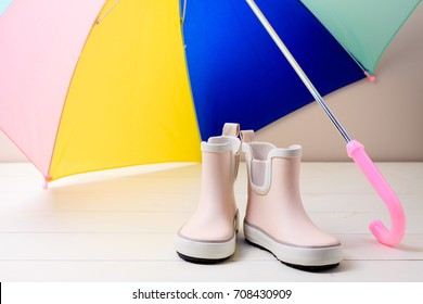 Pink little children rubber boots stand under colorful umbrella, concept of autumn or spring background.