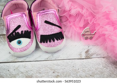 Pink little girlie baby shoes on a wooden floor