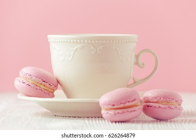 pink macaron handmade with a cup of coffee on pink background toned, selective focus