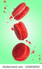 Pink macarons cookies in motion. French cakes. Sweet and colorful French macaroons fall or fly in motion. With slices on a green background, and flying particles. Vertical photo