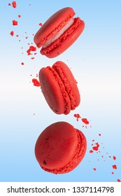 Pink macarons cookies in motion. French cakes. Sweet and colorful French macaroons fall or fly in motion. With slices on a blue background, and flying particles. Vertical photo