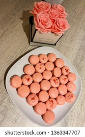 Pink macarons on white plate. Pink roses in background.