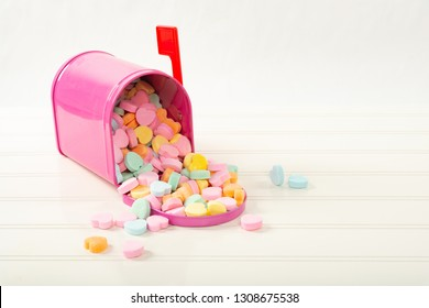 Pink mailbox full of candy hearts on a white bead board table with a shallow depth of field and copy space