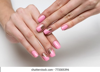 pink manicure with gold design on long square nails on a white background