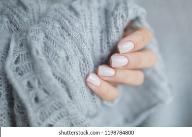 Pink manicure nails with a grey scarf