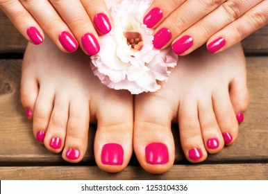 Pink manicure and pedicure with flower close-up, isolated on a wooden background, top view