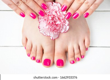 Pink manicure and pedicure with a flower on white wooden background, top view.