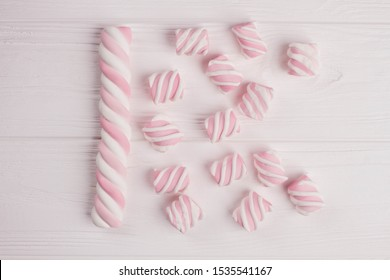Pink marshmallow on wooden background. Delicious sweets on white wooden table.