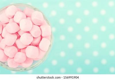 Pink marshmallows on polkadot blue blurred background with vintage nostalgic editing