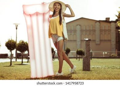 Pink mattress. Bewitching dazzling smiling beaming glowing long-haired joyful beauty wearing hat and yellow top standing with a pink inflatable air mattress outdoors.