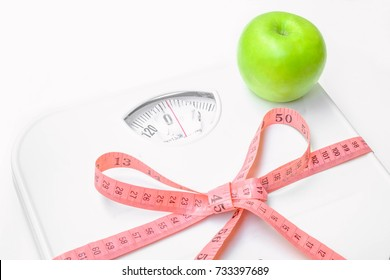 Pink measuring tape wrapped around the Weight scales. And the green apple is placed on top.Selective focus,Conception about health care