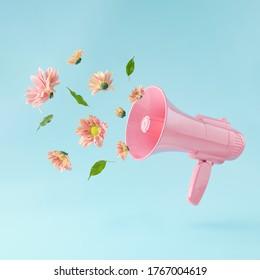 rosafarbene Megaphone mit bunten Sommerblumen und grünen Blättern auf pastellblauem Hintergrund. Werbung. Minimales Naturkonzept.