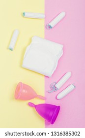 Pink menstrual cup on color background, female intimate hygiene period products, top view