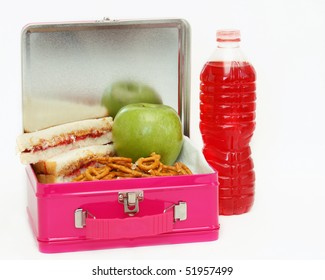 Pink metal lunchbox filled with peanut butter and jelly sandwich, pretzels and an apple with a drink to the side on an isolated white background