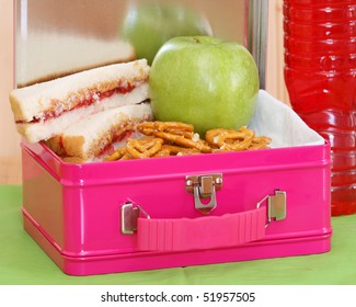 pink metal lunchbox with peanut butter and jelly sandwich, pretzels, apple and red drink on a green placemat close up horizontal composition
