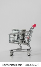 Pink and metal shopping cart on white background with  one hundred dollars banknote.  Minimalism style. Shop trolley at supermarket. Sale, discount, shopaholism, black friday concept
