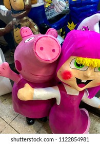 Pink Mexican piñatas in the shape of a little pig and a girl -used for birthday celebrations.
