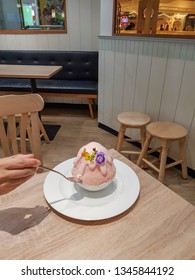 Pink milk kakigori or Japanese shaved ice dessert flavored, Topped with many flower