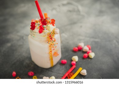 Pink milkshake with whipped cream, dripping sauce and candy's on table
