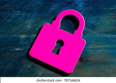 pink miniature bag, key on the keyhole on the blue wood texture