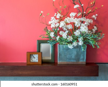 Pink modern interior wall with artificial flowers in ceramic vase