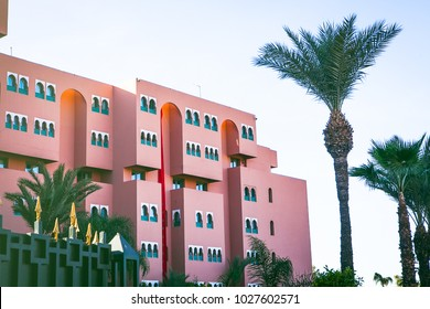 Pink modern moroccan building with palm trees and windows