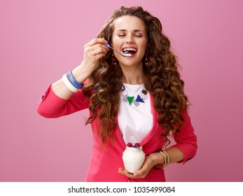 Pink Mood. happy modern woman with long wavy brunette hair on pink background enjoying farm organic yogurt