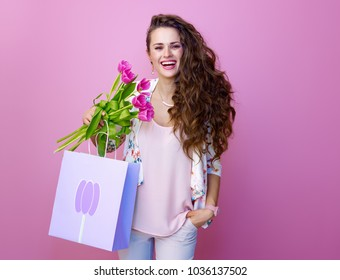 Pink Mood. happy modern woman with long wavy brunette hair isolated on pink with a bouquet of tulips and shopping bag