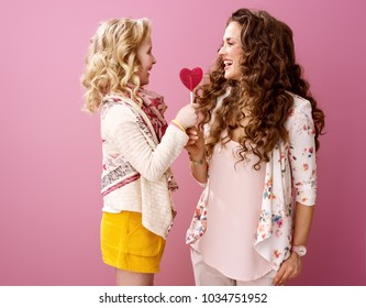 Pink Mood. happy stylish mother and daughter with wavy hair on pink background holding heart shaped lollipop