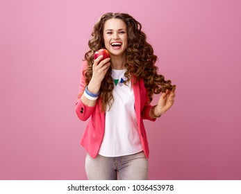 Pink Mood. happy stylish woman with long wavy brunette hair on pink background eating an apple