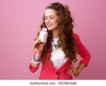 Pink Mood. happy trendy woman with long wavy brunette hair isolated on pink background drinking farm organic yogurt